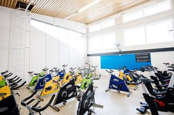Dedicated spin class room containing 24 bikes, arranged facing one bike for the spin-class instructor