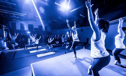 Students being led by fitness instructors in an exercise class at Les Mills gym