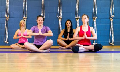 Four students sitting on the gym floor with hands bowed in prayer position in the sport and recreation centre