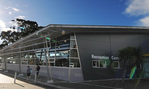 Exterior of the corner of the Recreation Centre building, with two people walking outside, wearing gym gear