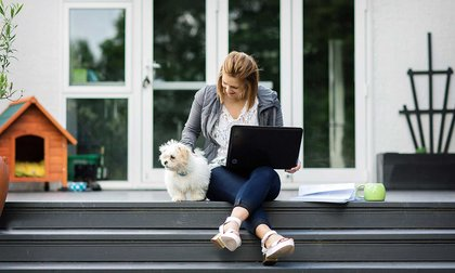 Person sitting on the top step of a deck with a laptop balanced on their knees, patting a small white furry dog