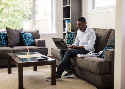 One person sitting on a couch typing on a laptop which is balanced on their knee
