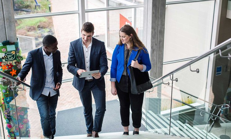 Three people in corporate attire walking up stairs, talking and looking at tablet