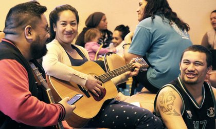 Person strumming a guitar with two other students smiling and talking