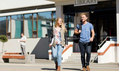 Two students walking outside library