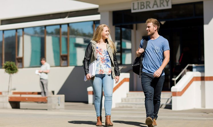 Two students walking away from the campus library