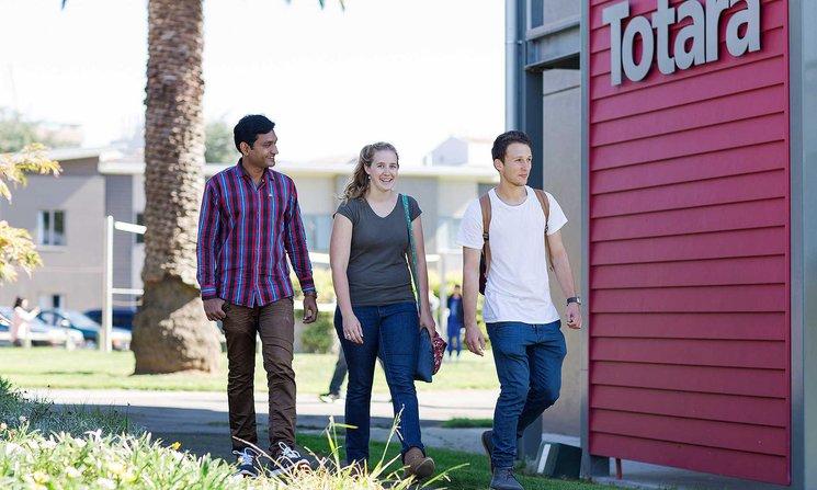 Three students walking past the Totara accommodation building