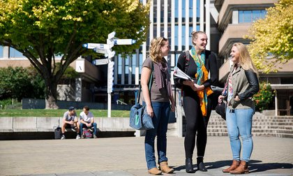 Three students standing on the campus concourse, with buildings and a signpost in the background