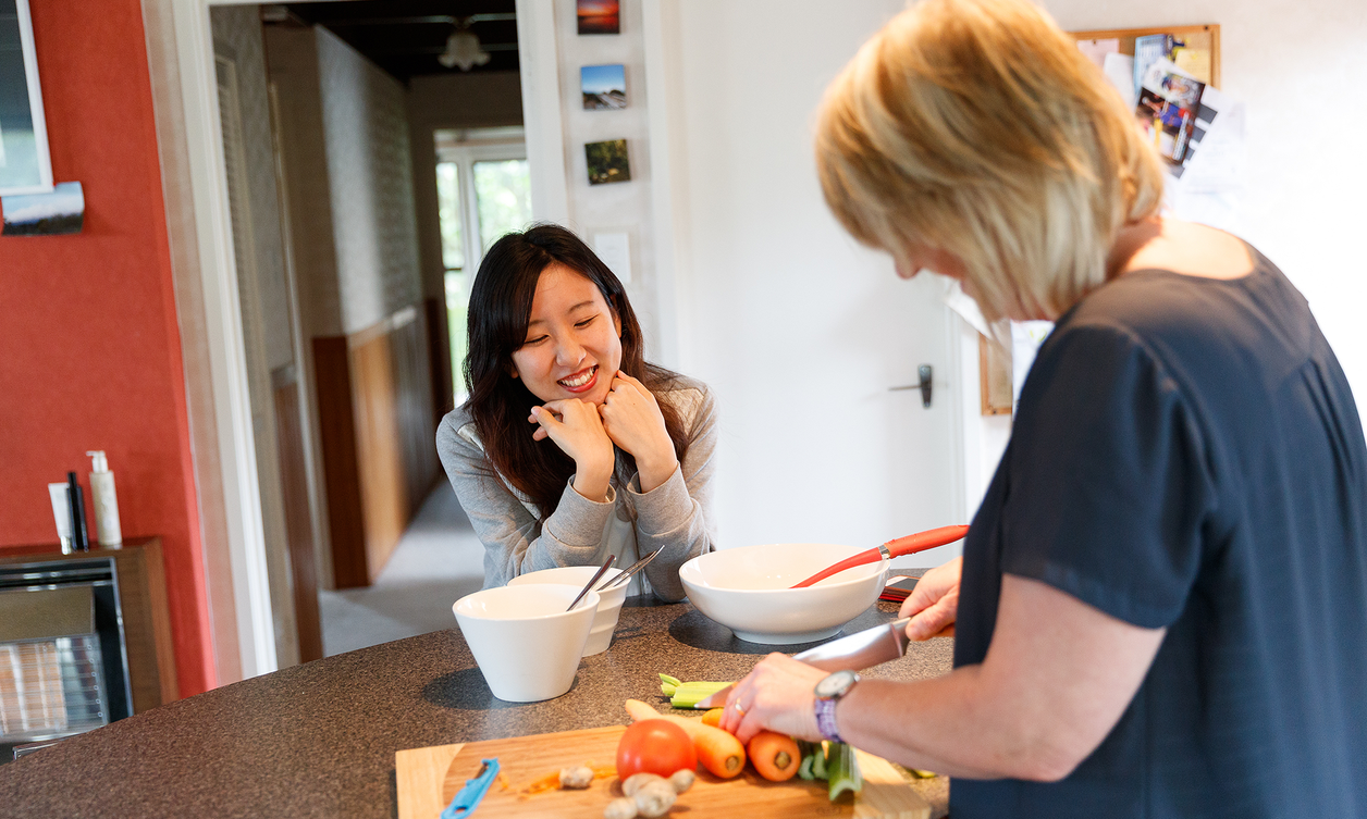 Two people standing at a kitchen bench while they prepare a range of vegetables