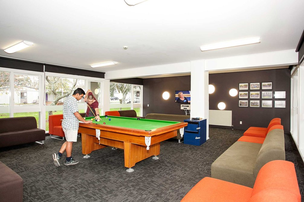 Lounge in Colombo Hall with two students playing a game of pool