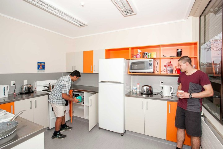 Colombo Hall's kitchen with cupboards, fridge and oven, and two students preparing a hot drink