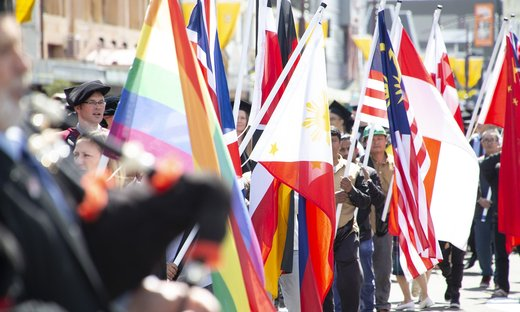 People attending a graduation procession, holding the colourful flags of different countries