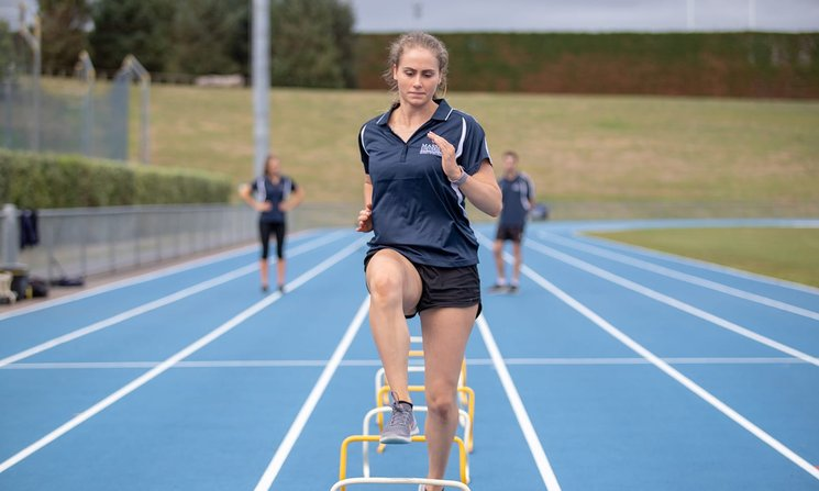 Student stepping over small hurdles on an athletics track