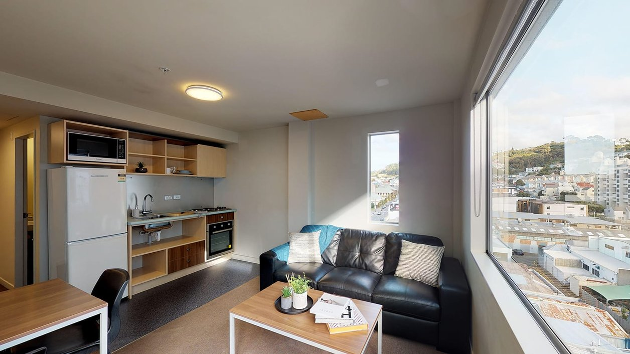 Lounge in The Cube apartment, with fridge, kitchenette, tables and couch and Wellington city views