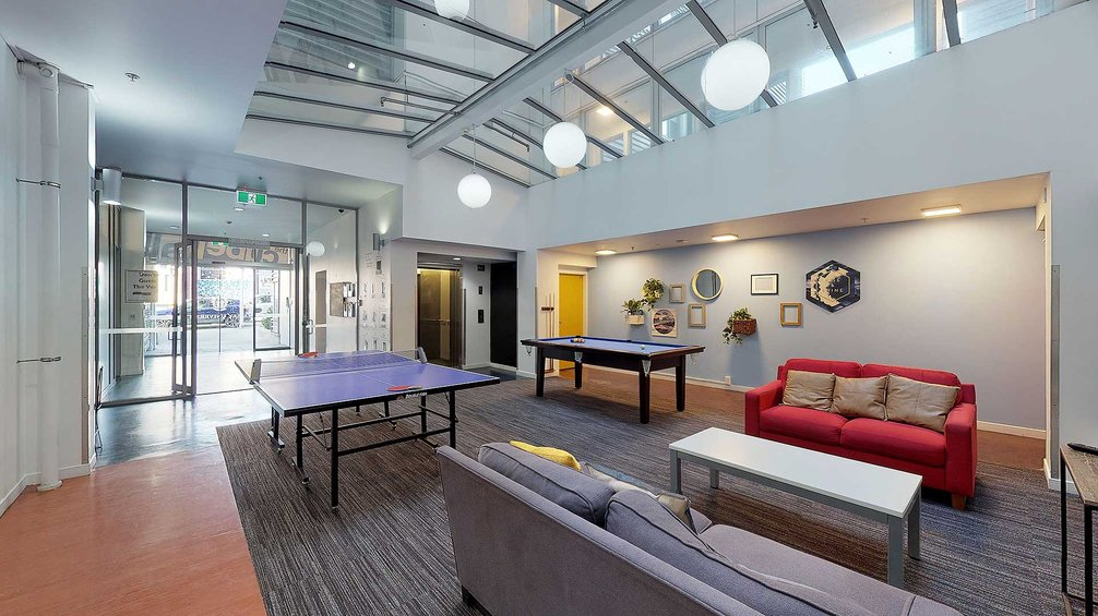 Interior of the Cube Hall common room with table tennis table, pool table, a coffee table and two couches