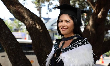 Close-up of Anezka Hoskin wearing a traditional Maori cloak, with big tree trunks in the background