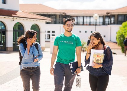 Three students talking and laughing on campus