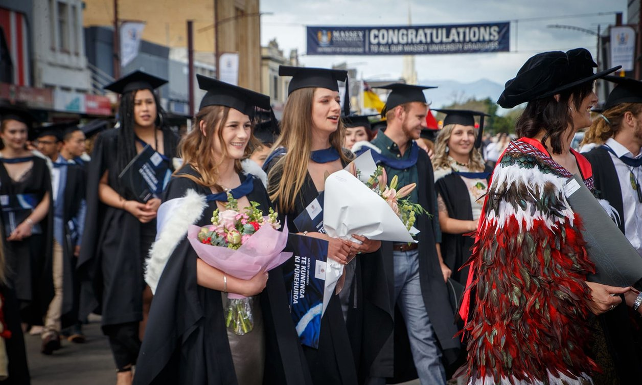 Graduates holding large flower bouquets, dressed in graduation attire, walking in a graduation procession