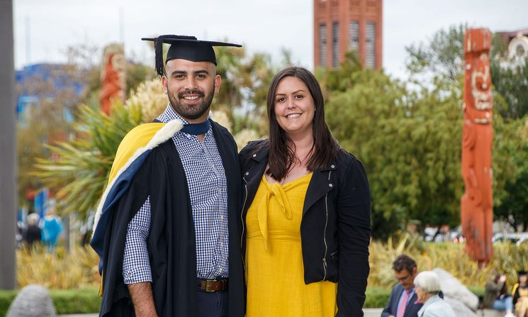 A graduate in graduation attire standing next to a support person, with the campus in the background showing Maori wooden carvings