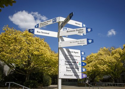 Signpost of building names, with campus buildings and trees in the background