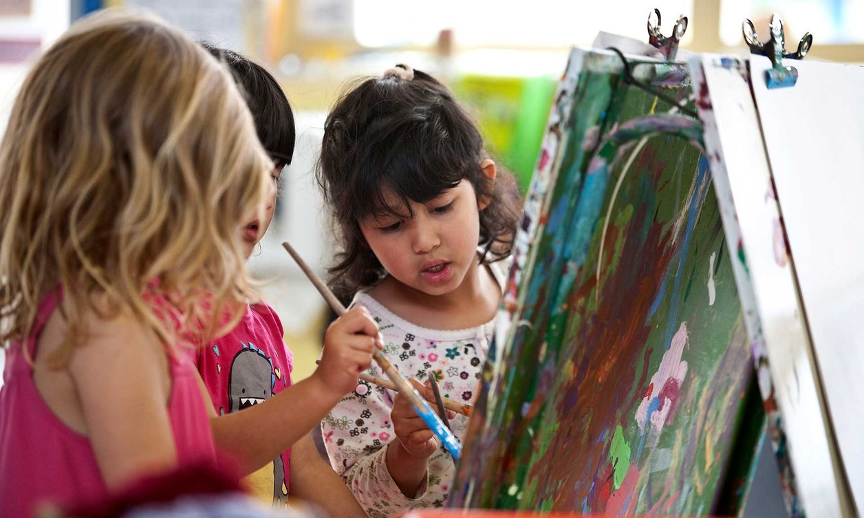Three children holding paint brushes while painting at Massey University Childcare