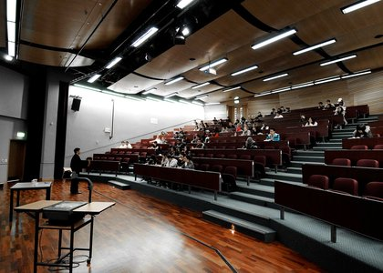 Lecture theatre half-filled with seated students