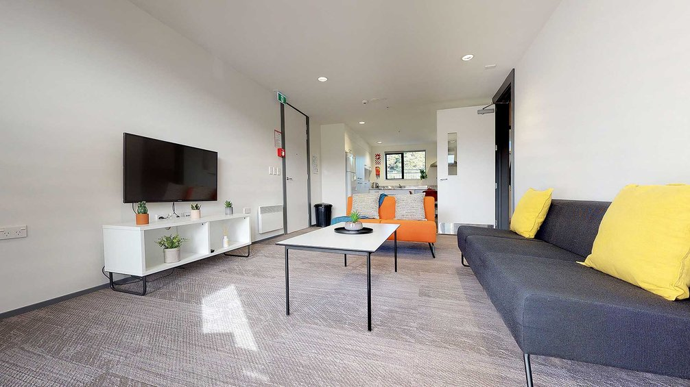 Matipo, Titoki and Tānekaha apartments' lounge area with couches, coffee table and wall mounted TV