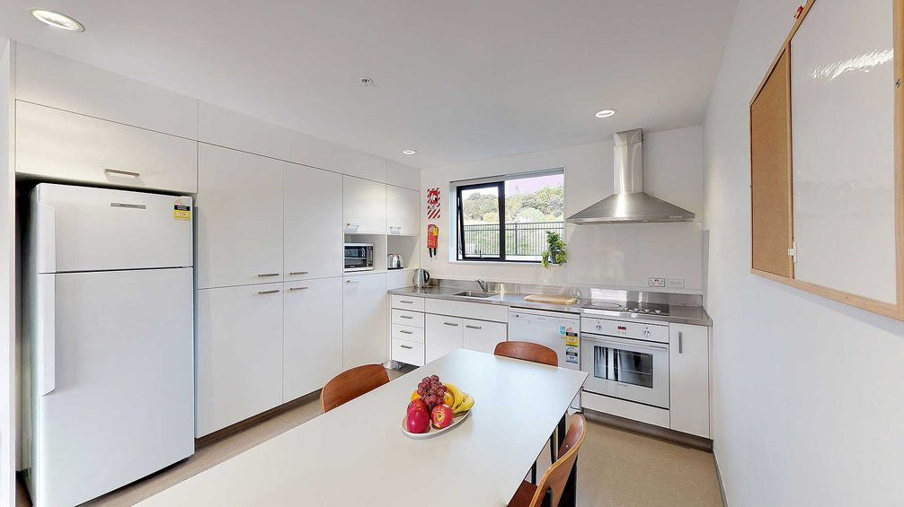 Matipo, Titoki and Tānekaha apartments' kitchen with fridge, bench top, oven and a dining table with chairs