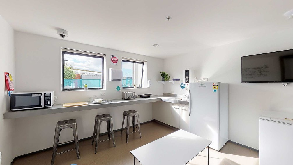 Pūkeko, Tui and Weka halls' kitchen with bench tops, a fridge, a microwave and bar stools