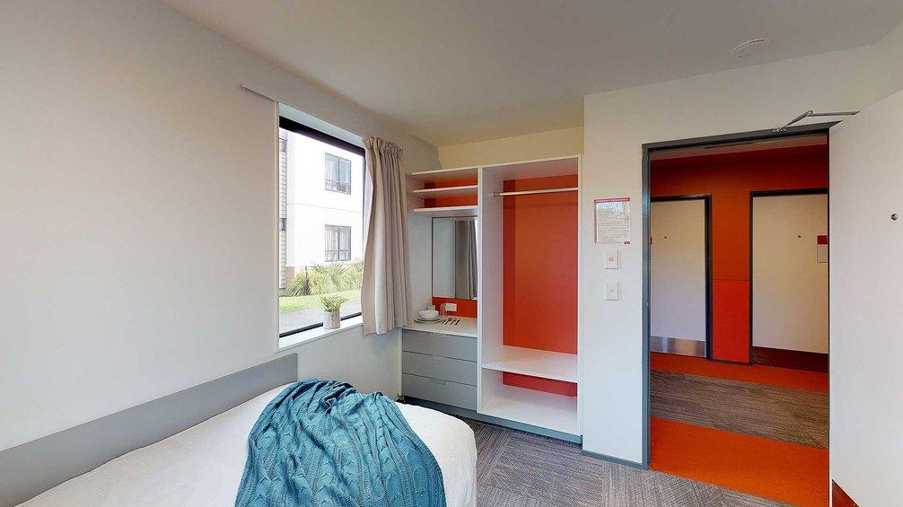 Pūkeko, Tui and Weka halls' single bedroom with bed, drawers and wardrobe