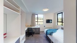 Studio unit with a bed, desk, chair and built-in storage