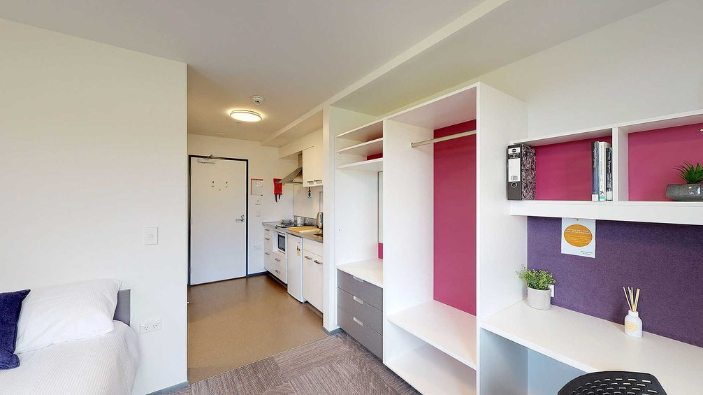 Studio Unit with bed, desk, wardrobe, and kitchenette