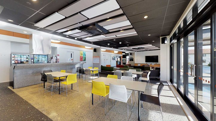 Te Rito's large, airy common area with four dining tables and chairs