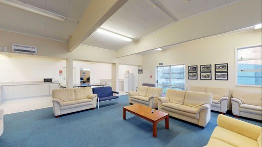 Interior of Atawhai Flats common room, with 7 couches and a coffee table