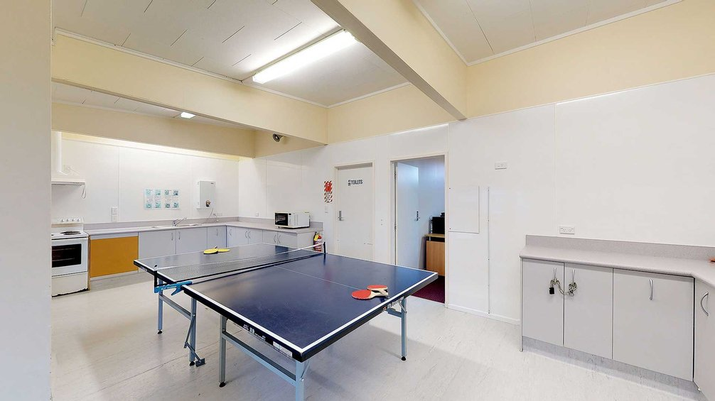 Interior of Atawhai Flats common room with table tennis table, kitchenette and cupboards
