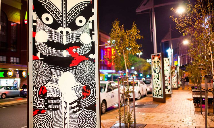 Night street scene, showing pillars with unique black and red Maori designs