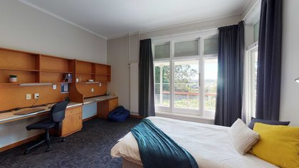 Interior of Bindaloe Hall's double bedroom with bed, dual built-in desks and a large window