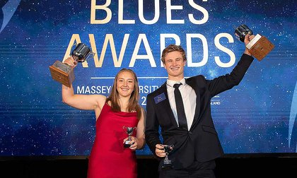 Two students holding up silver trophies on stage at the Blues Awards