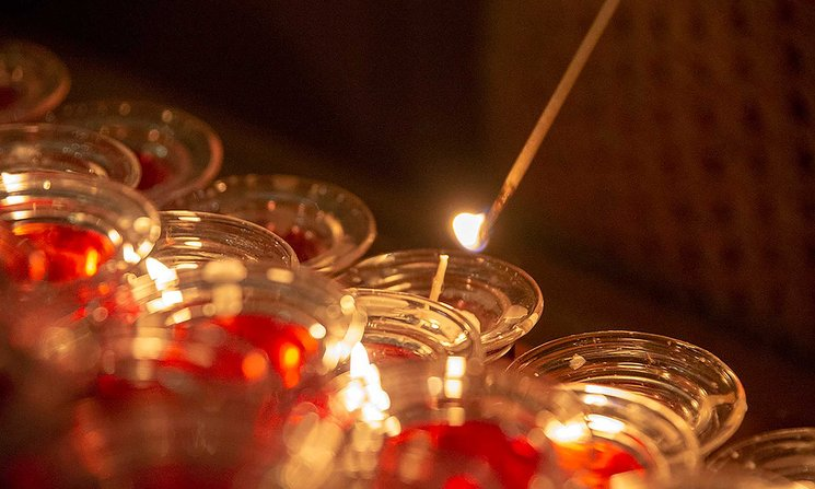Close-up of a multitude of candles in small glass holders, with one being lit