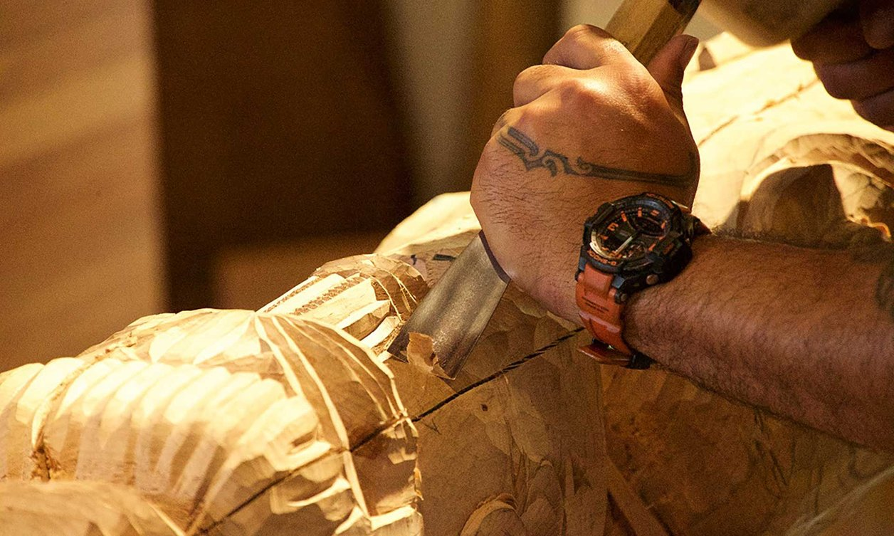 Close-up of a carver creating a traditional Māori carving