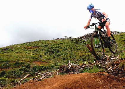 Mountain bike rider airborne while crossing rugged terrain, and wearing a mask