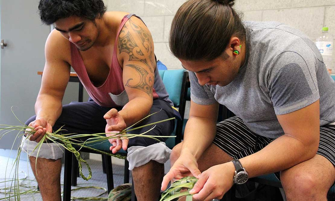 Two students weaving with flax