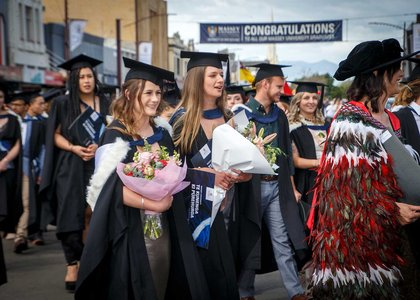 Graduates in procession wearing academic dress