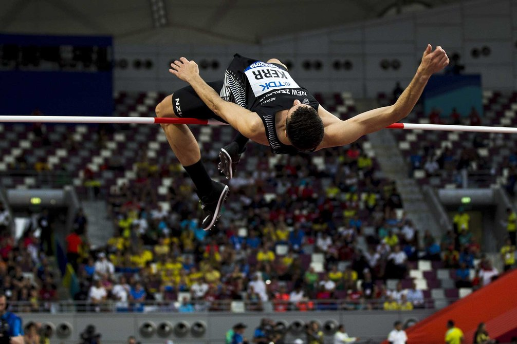 Athlete in mid-air over the high jump, with a crowd seated in the stands