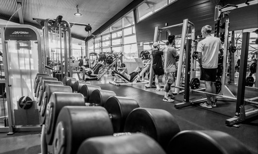Black and white photo of students sharing the gym facilities