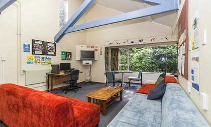 Kiwitea lounge with couches, coffee table, computer desk, TV and garden views