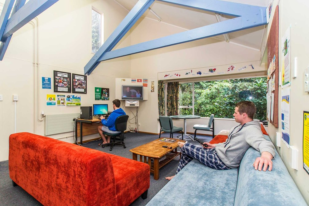 Interior of Kiwitea accommodation lounge, with students relaxing on couch and sitting at a computer