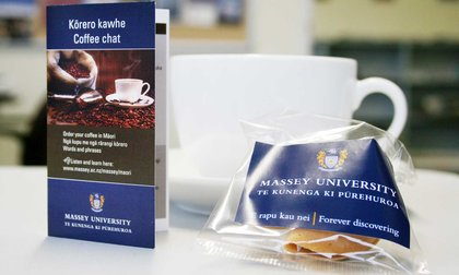 Close-up of a coffee cup and a pamphlet on how to order coffee in te reo Māori