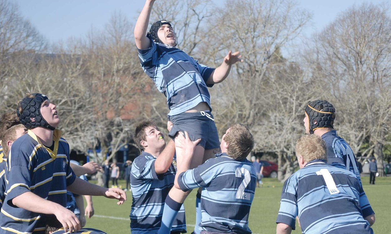 Rugby player being lifted to reach the ball, by fellow team players