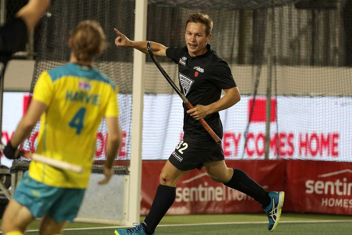 Two teams playing field hockey, with one player scoring a goal and celebrating